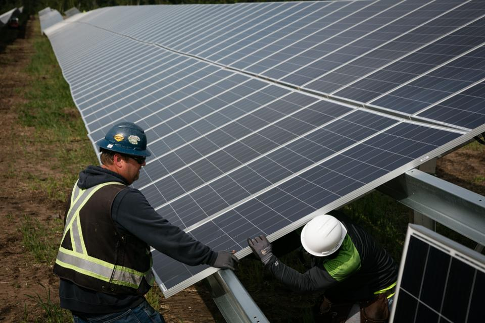 Workers install solar panels at the Connexus Energy Athens Township solar-plus-storage project site