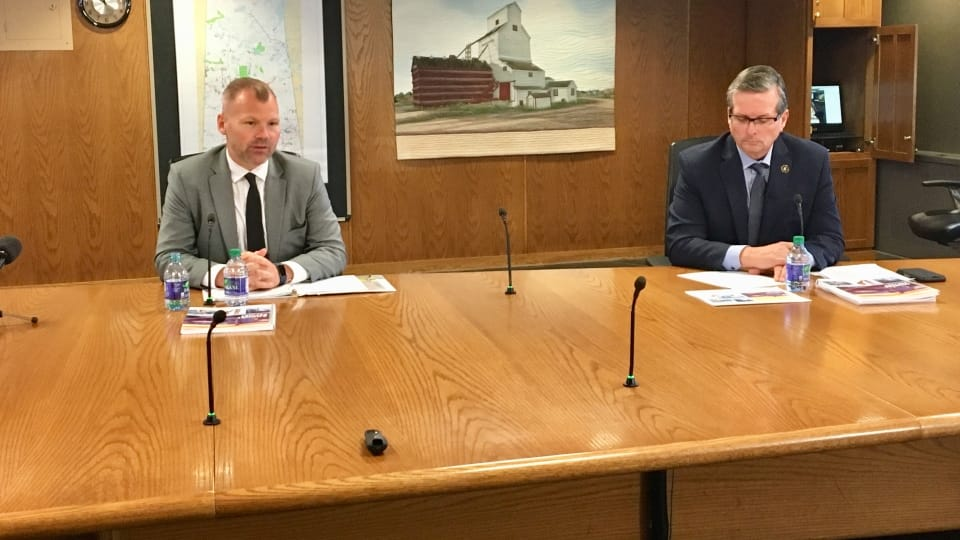 Minister Responsible for SaskPower Dustin Duncan, left, and SaskPower President and CEO Mike Marsh, right, present the Crown corporations 2019-20 report.