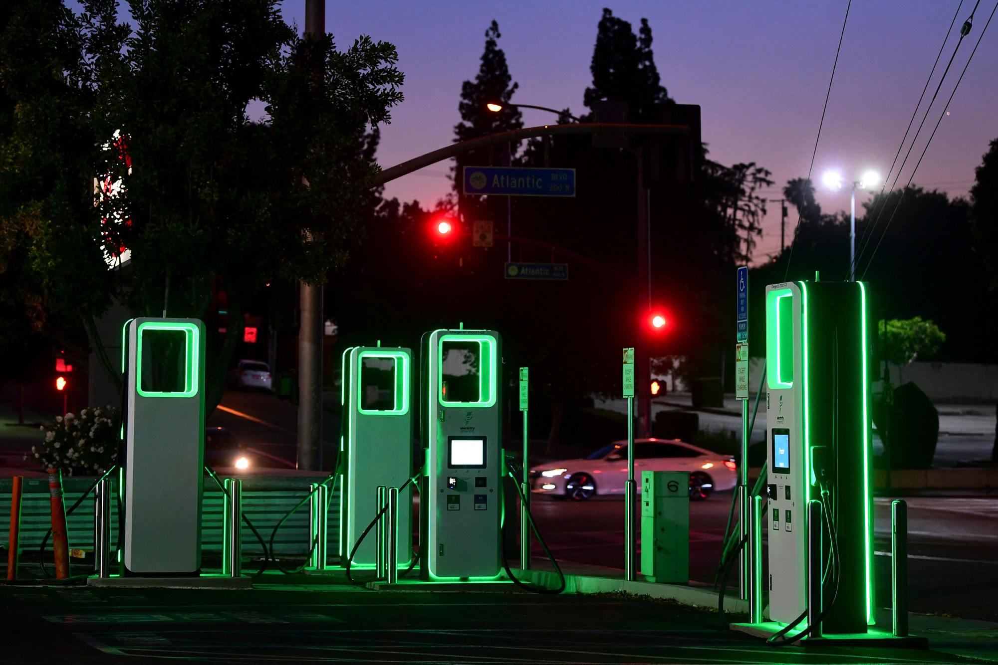 An electric vehicle charging station lights up green in the parking lot of a Ralph's supermarket in Monterey Park, Calif.