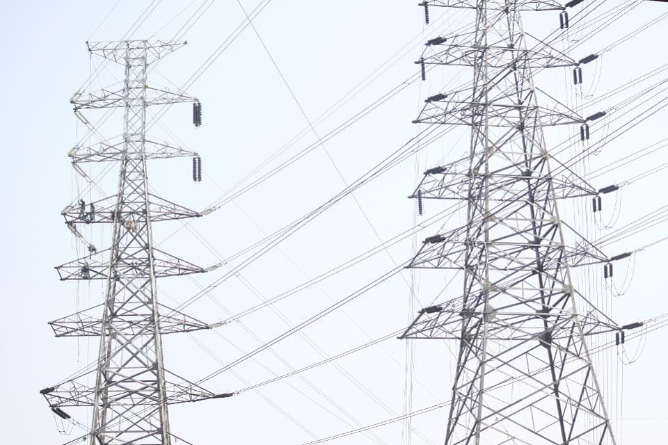 Workers assemble electricity installations in high voltage towers