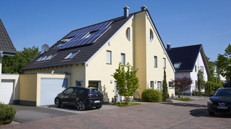 Tech Revolution: A house with solar panels and an electric vehicle parked outside.