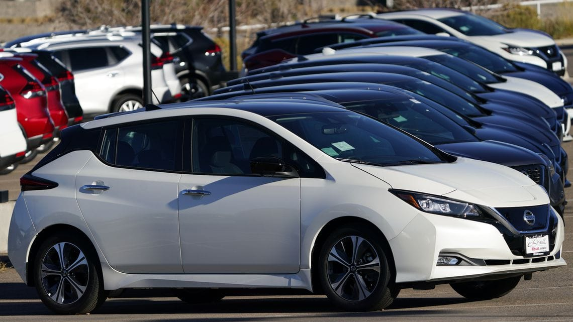A long line of unsold 2021 Leaf electric vehicles sits at a Nissan dealership Nov. 8, 2020, in Highlands Ranch, Colo