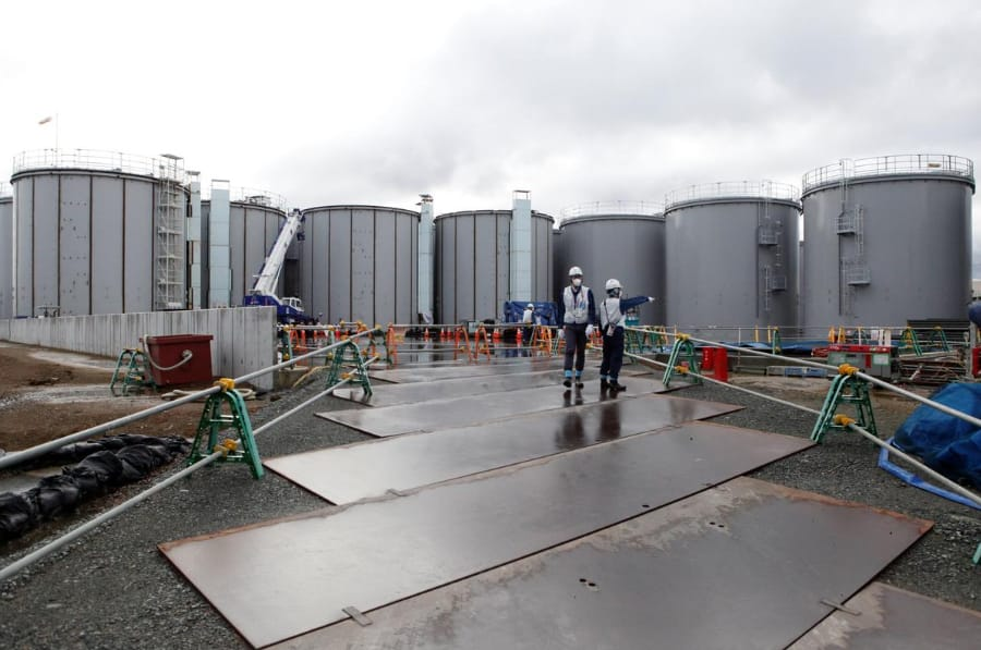 Workers are seen near storage tanks for radioactive water at Tokyo Electric Power Co's (TEPCO) tsunami-crippled Fukushima Daiichi nuclear power plant
