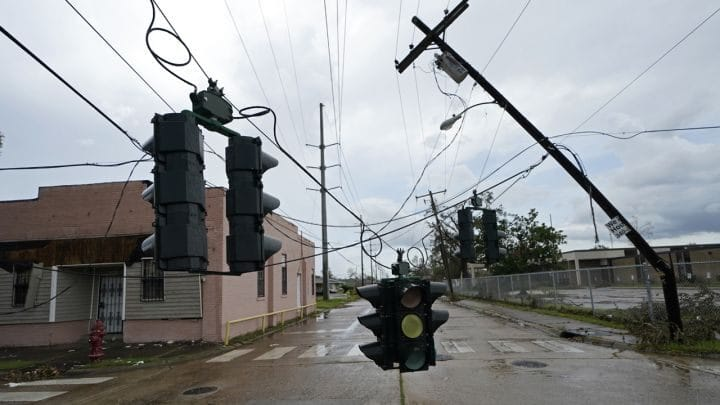 Traffic signals dangle close to the roadway from broken utility poles in Lake Charles, La
