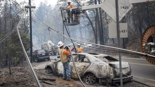 AT&T workers repair phone lines as a burned-out vehicle sits on a road during the Camp Fire in Paradise, California,