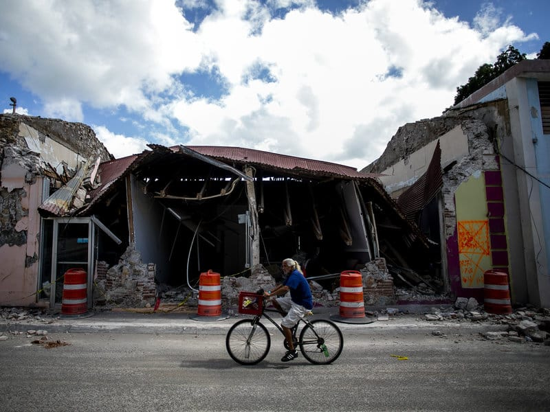 A cyclist rides past a destroyed building in Guanica, Puerto Rico. The island was hit by a series of earthquakes over the past couple of weeks