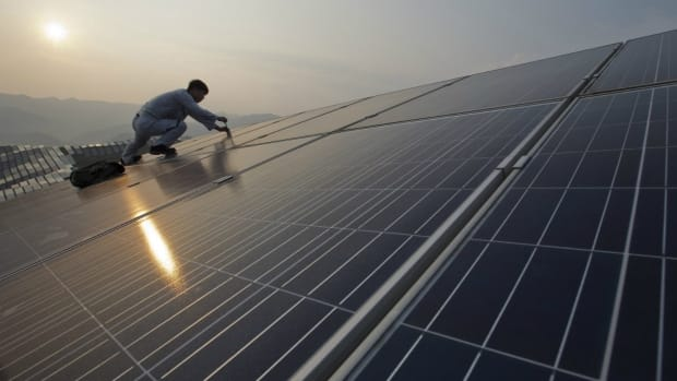 A worker performs maintenance work on solar panels at a photovoltaic power station