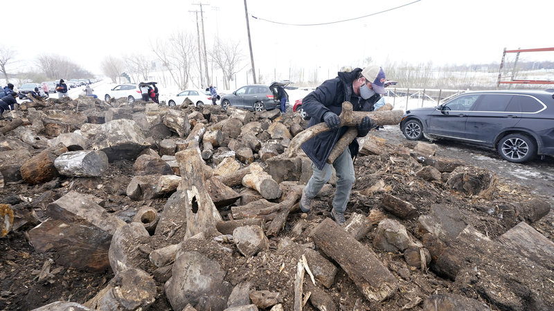 People collect firewood with others from a wood heap opened to the public on Wednesday in Dallas